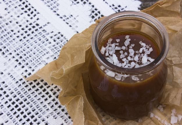 Kom met gezouten karamel en suikergoed op houten achtergrond, ruimte voor tekst