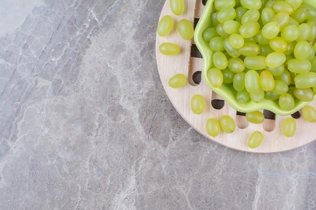 Kom met groene druiven op houten stuk.