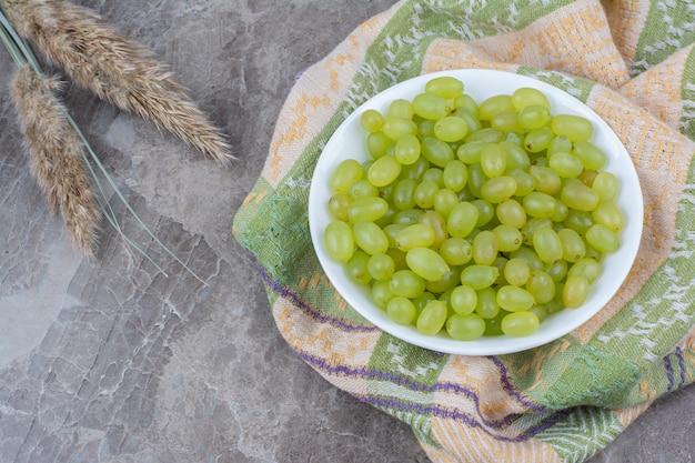 Kom met groene druiven op kleurrijk tafelkleed.