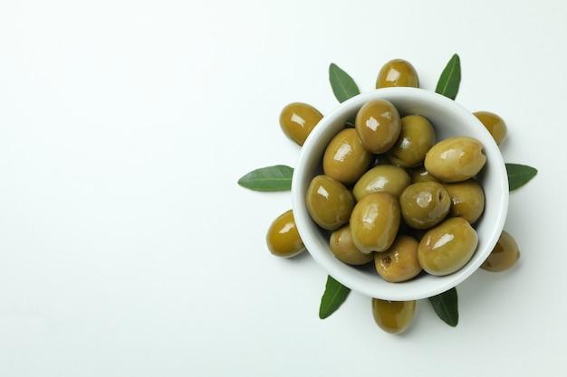 Kom met groene olijven en bladeren op witte achtergrond