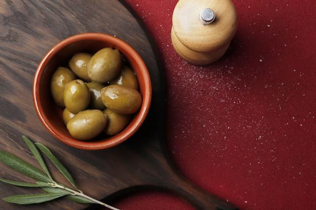 Kom met groene olijven op een rode tafel, ruimte voor tekst.