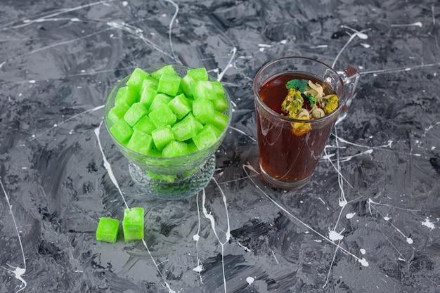 Kom met groene suikerklontjes en kopje thee op marmeren oppervlak.