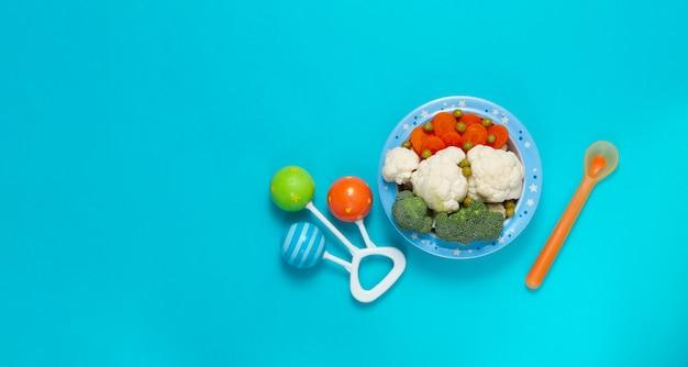 Kom met groenten en fruit, babyvoeding, rammelaar en lepel, op een blauwe achtergrond, bovenaanzicht, horizontaal.