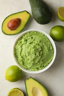 Kom met guacamole, avocado en limoen op witte gestructureerde achtergrond, bovenaanzicht