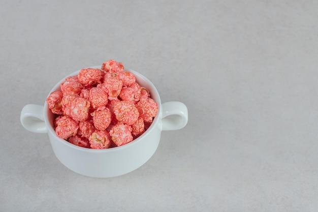 Kom met handvatten met rode gecoate popcorn op marmeren tafel.