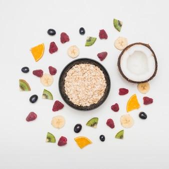 Kom met haver en gehalveerde kokosnootpasta met frambozen; druiven; banaan; kiwi plakjes op witte achtergrond