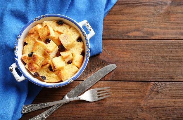 Kom met heerlijke broodpudding en servet op houten tafel