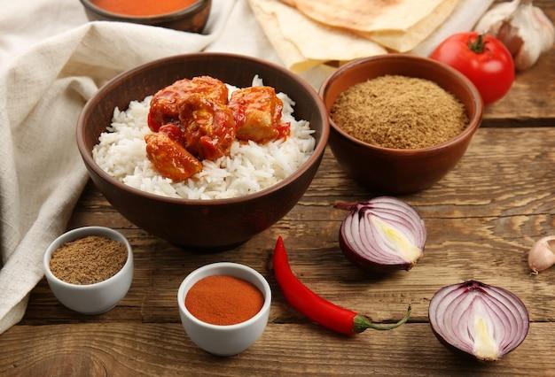 Kom met heerlijke kip tikka masala, rijst en kruiden op houten tafel