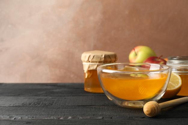 Kom met honing, beer en vruchten op houten achtergrond, ruimte voor tekst
