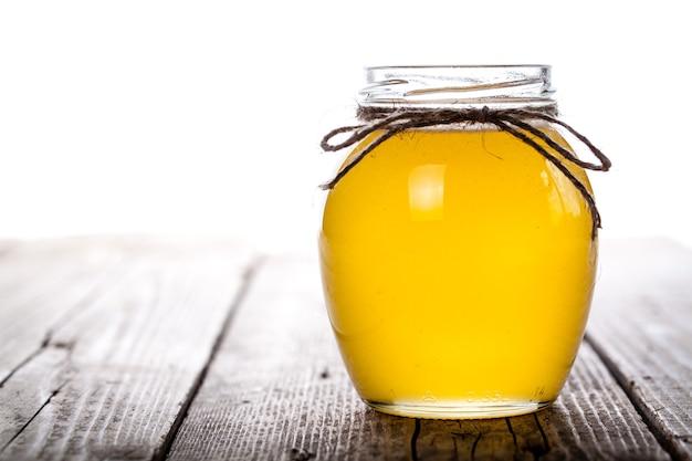 Kom met honing op houten tafel. symbool van gezond leven en natuurlijke geneeskunde. aromatisch en smakelijk.