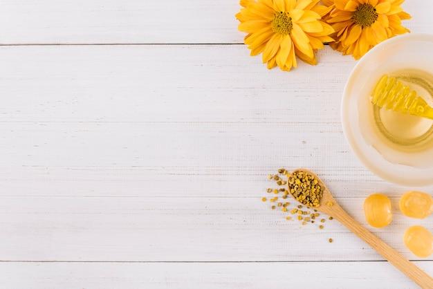 Kom met honing; snoepjes; bijenpollen zaden en bloemen op houten achtergrond