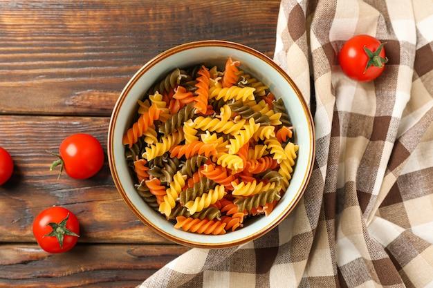 Kom met kleurendeegwaren, tomaten en keukenhanddoek op houten achtergrond, ruimte voor tekst