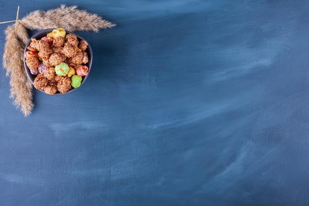 Kom met kleurrijke graanballen die op een blauwe achtergrond worden geplaatst.