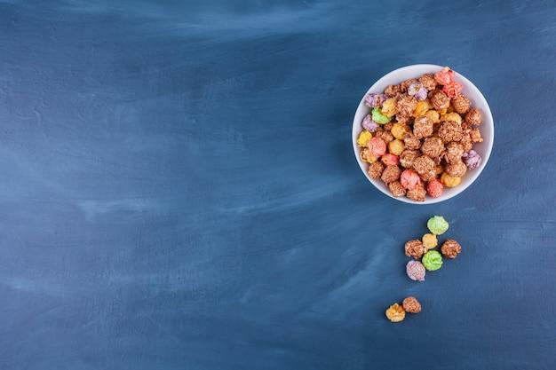 Kom met kleurrijke graangewassenballen die op een blauw worden geplaatst.
