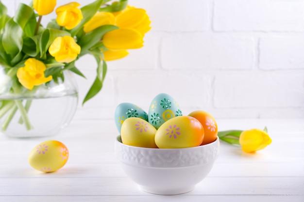 Kom met kleurrijke paaseieren, de decoratie van de lentepasen op witte houten lijst met boeket van gele tulpenbloemen in glasvaas op witte achtergrond. pasen interieurdecoratie