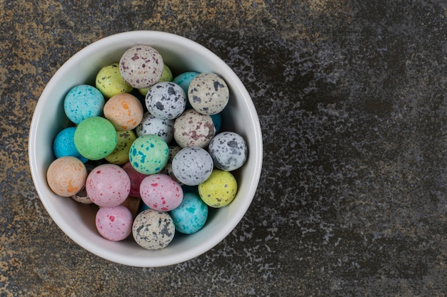 Kom met kleurrijke snoepjes op marmer.