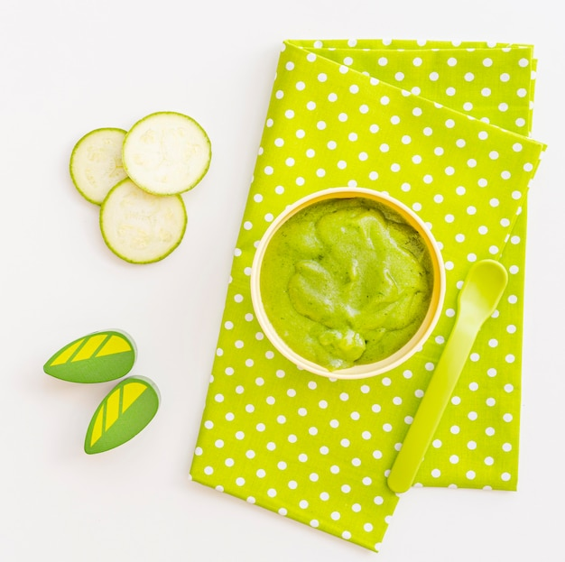 Kom met komkommerpuree voor baby op bureau