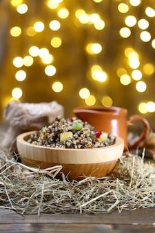 Kom met kutia - traditionele zoete kerstmaaltijd in oekraïne, wit-rusland en polen, op houten tafel, op een helder oppervlak