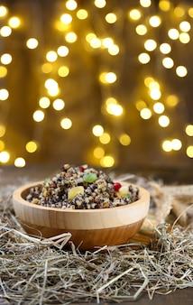 Kom met kutia - traditionele zoete kerstmaaltijd in oekraïne, wit-rusland en polen, op houten tafel