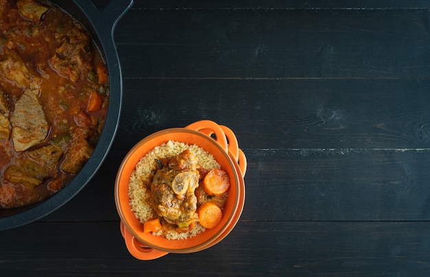 Kom met lam met groenten en couscous op zwarte houten achtergrond. ramadan-concept. ruimte kopiëren. bovenaanzicht.