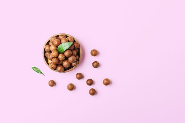 Kom met macadamia noten op een roze tafel. bovenaanzicht