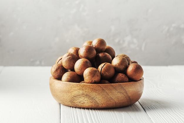 Kom met macadamia noten op een witte houten tafel.