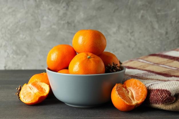 Kom met mandarijnen en plaid op donkere houten tafel