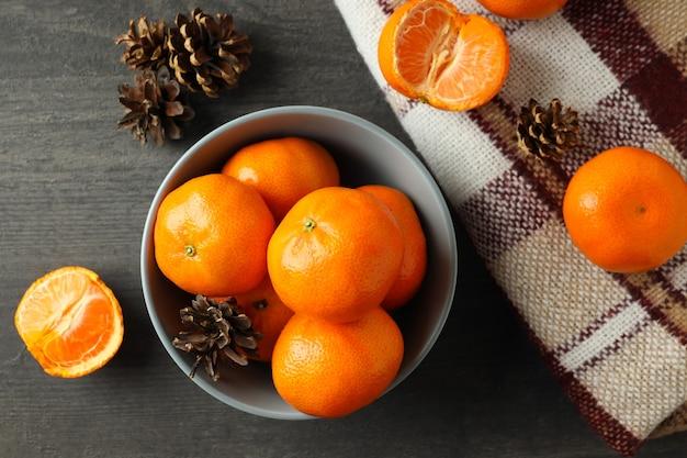 Kom met mandarijnen, kegels en plaid op donkere houten tafel