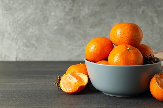 Kom met mandarijnen op donkere houten tafel