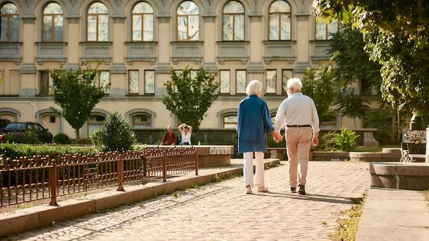 Kom met me mee achteraanzicht van bejaarde echtpaar hand in hand terwijl ze samen buiten wandelen