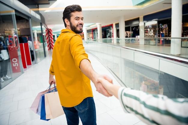 Kom met mij mee. foto van een vrolijke knappe kerel die vriendin leidt naar een geheime verrassingsplaats, draagt veel tassen, loopt in het winkelcentrum, een brede glimlachende shopper draagt een casual outfit binnenshuis