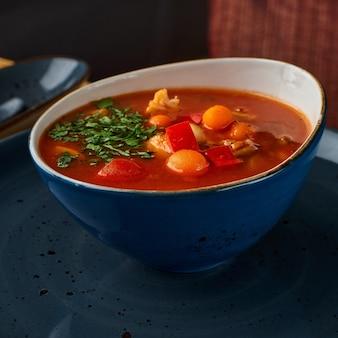 Kom met minestrone soep op een tafel in een restaurant.
