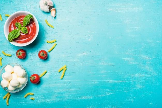 Kom met mozzarella ballen met tomatensaus; knoflook en pasta op turkooizen achtergrond