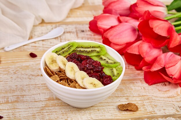 Kom met muesli, banaan, kiwi, bes met roze tulp bloemen