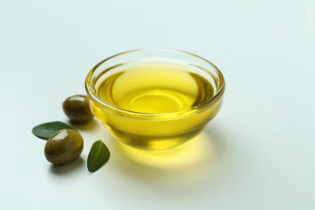 Kom met olie, olijven en bladeren op een witte ondergrond