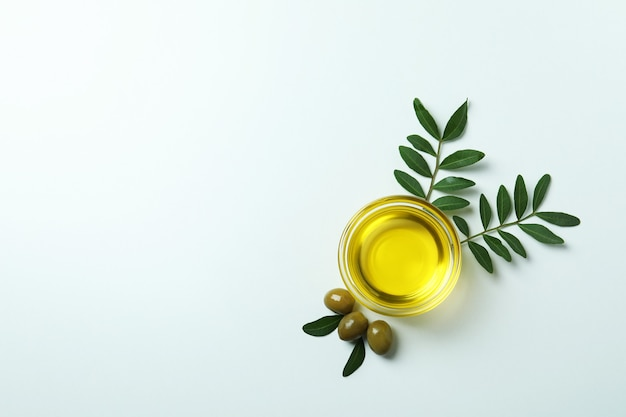Kom met olie, olijven en takjes op wit