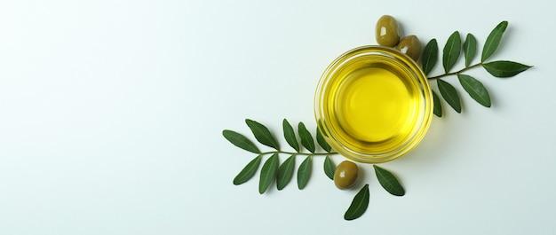 Kom met olie, olijven en twijgen op wit oppervlak