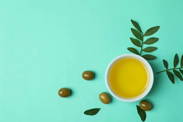 Kom met olijfolie, olijven en twijgen op muntoppervlak