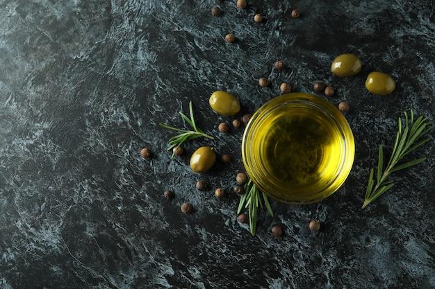 Kom met olijfolie, olijven, peper en rozemarijn op zwarte smokey-oppervlakte