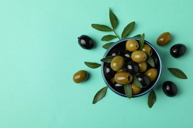 Kom met olijven en bladeren op muntachtergrond