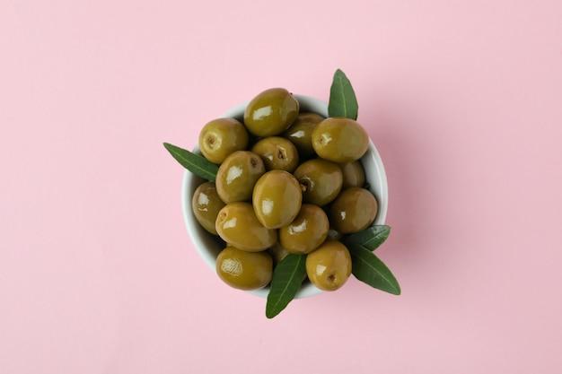 Kom met olijven en bladeren op roze achtergrond