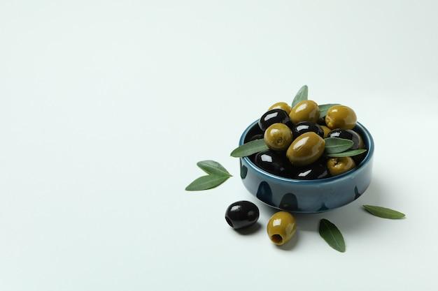 Kom met olijven en bladeren op witte achtergrond