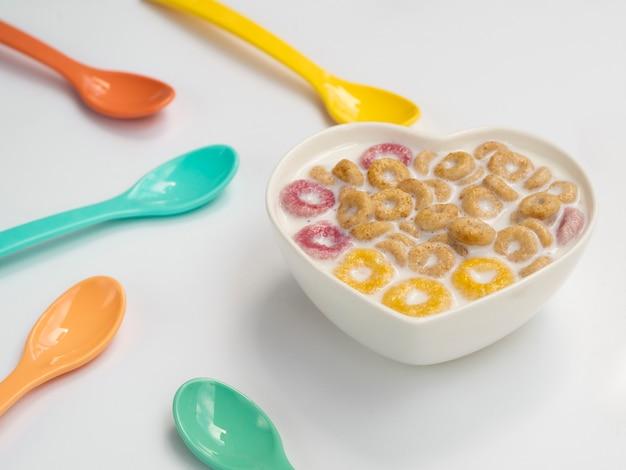 Kom met ontbijtgranen en lepels ernaast