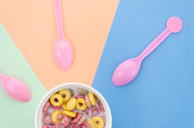 Kom met ontbijtgranen en roze schattige lepels