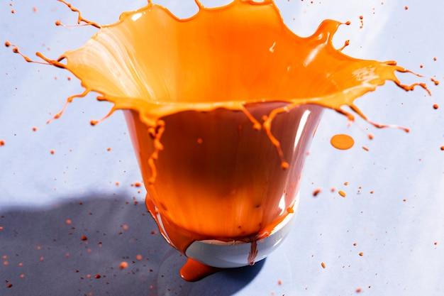 Kom met oranje verf en violette achtergrond