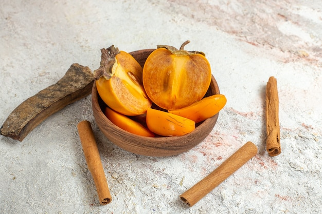 Kom met palm- en kaneelstokjes op wit marmer