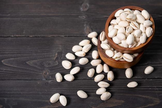 Kom met pistachenoten op een houten tafel.
