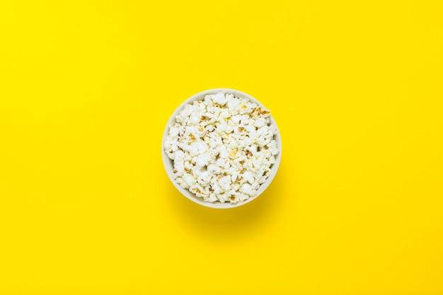 Kom met popcorn op een gele achtergrond. plat lag, bovenaanzicht.