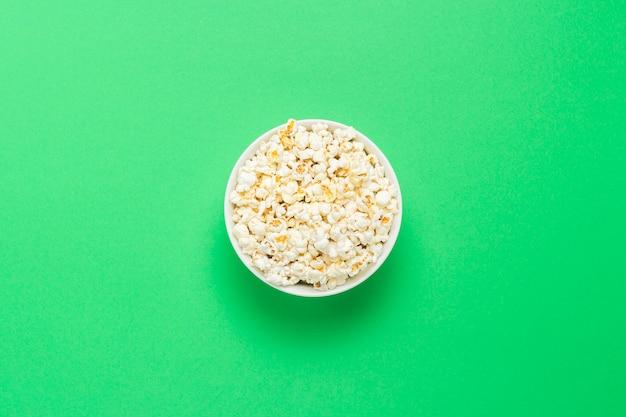 Kom met popcorn op een groene achtergrond. plat lag, bovenaanzicht.