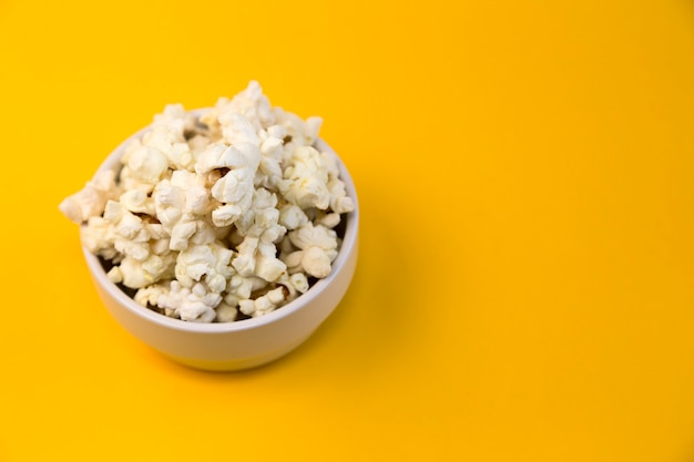 Kom met popcorn op gele achtergrond en ruimte voor tekst. thuisbioscoop.